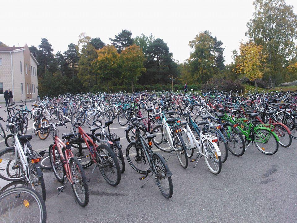 Kuvassa on paljon polkupyöriä pyörätelineissä koulupihalla.