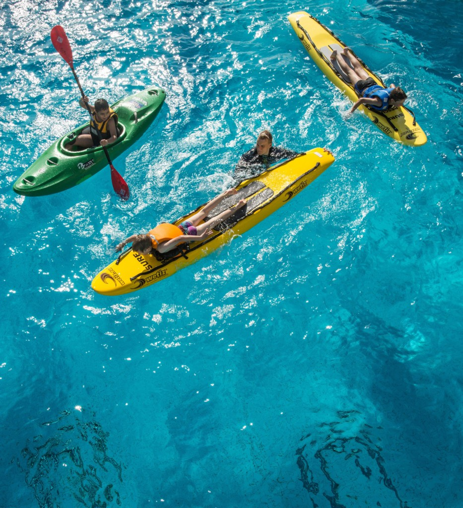 Yksi lapsi meloo ja kaksi lasta liikkuvat pelastulautoilla uima-altaassa. Ohjaaja on altaaassa auttamassa.