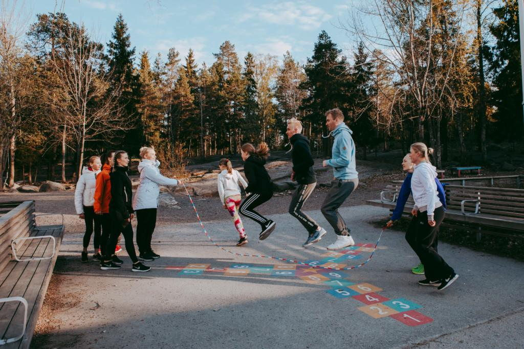 Kaksi pyörittää pitkää hyppynarua, jossa hyppii samanaikaisesti kolme hyppääjää. Lisäksi vuoroaan odottaa neljä hyppääjää.