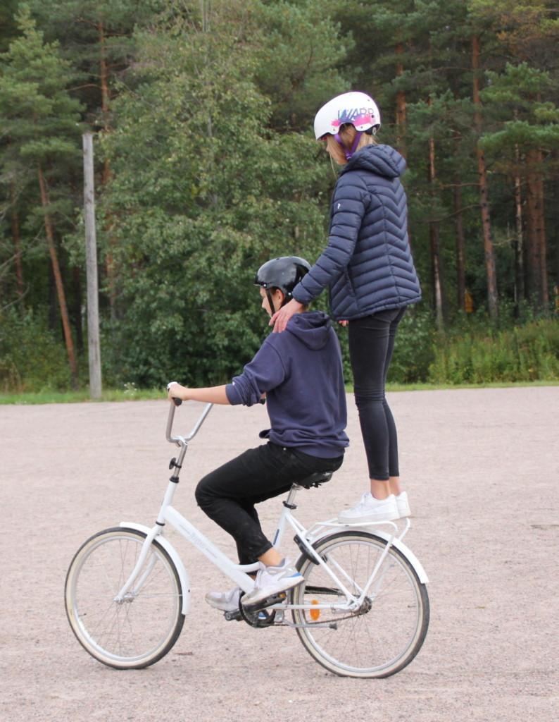 Poika ajaa pyörällä ja tyttö seisoo tarakalla pitäen pojan hartioista kiinni.