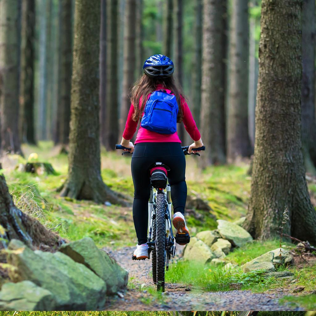 Tyttö ajaa pyörällä metsäpolkua pitkin reppu selässä.