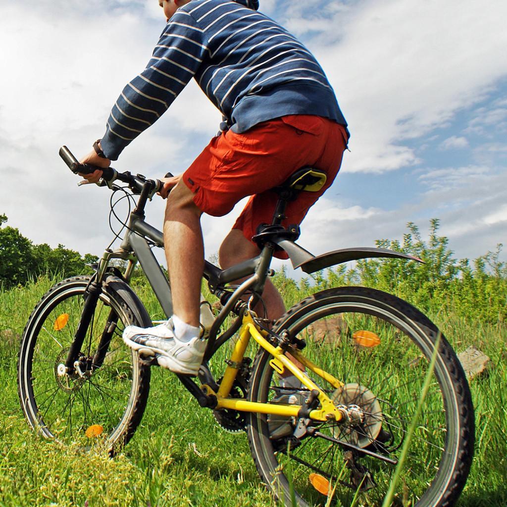 Poika ajaa pyörälllä niityllä.