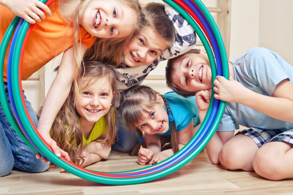 Lapset kurkkivat värikkäiden vanteiden läpi kameraa kohti.