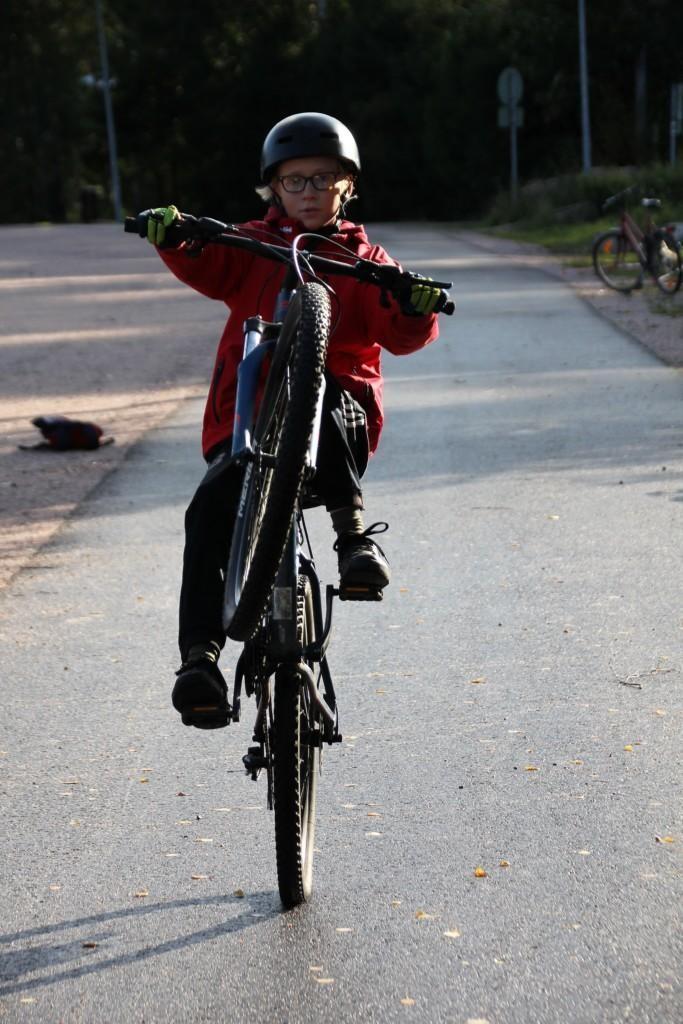 Poika keulii pyörällä kuvajaa kohti kypärä päässä.