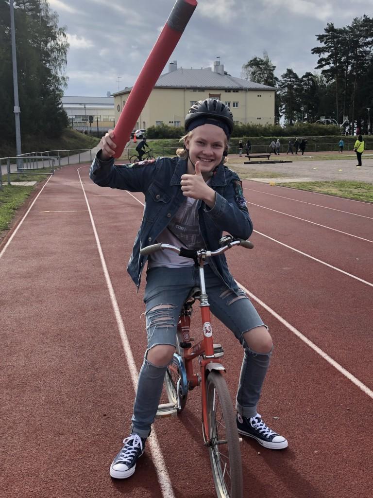Åpoika ostuu pyörän selässä ja heiluttaa ilmassa kisailussa käytettävää lötköpötköä.