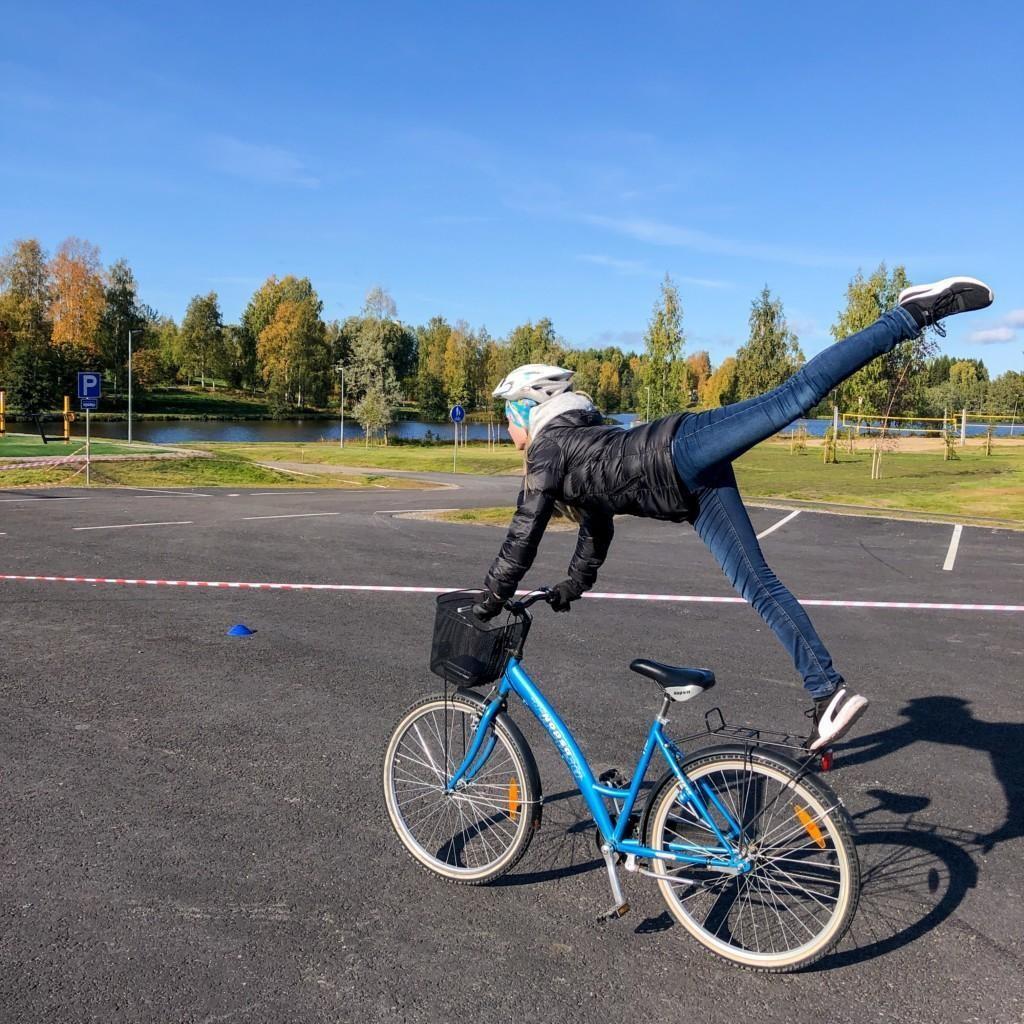 Tyttö temppuilee pyörän päällä ajaen. Kädet tangossa, tinen jalka tarakalla ja toinen takana suorana ilmassa.