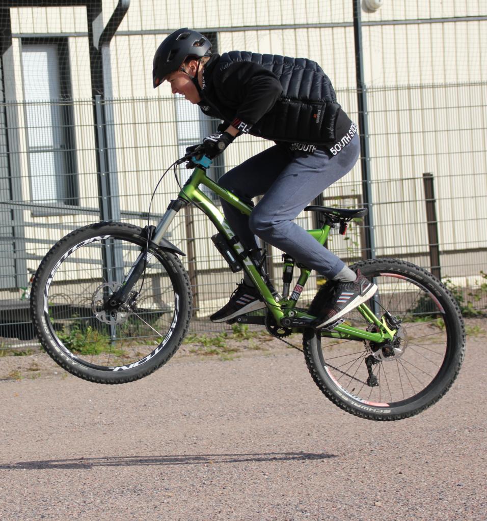 Poika hyppää ilmaan pyörän kanssa kypärä päässä.