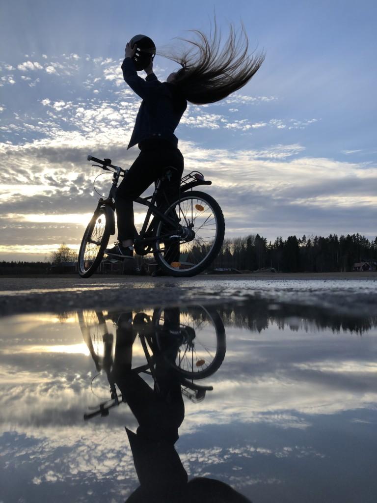 Tyttö istuu pyörän päällä, ottaa kypärää päästään auringonlaskua vasten ja heilauttaa hiuksiaan.