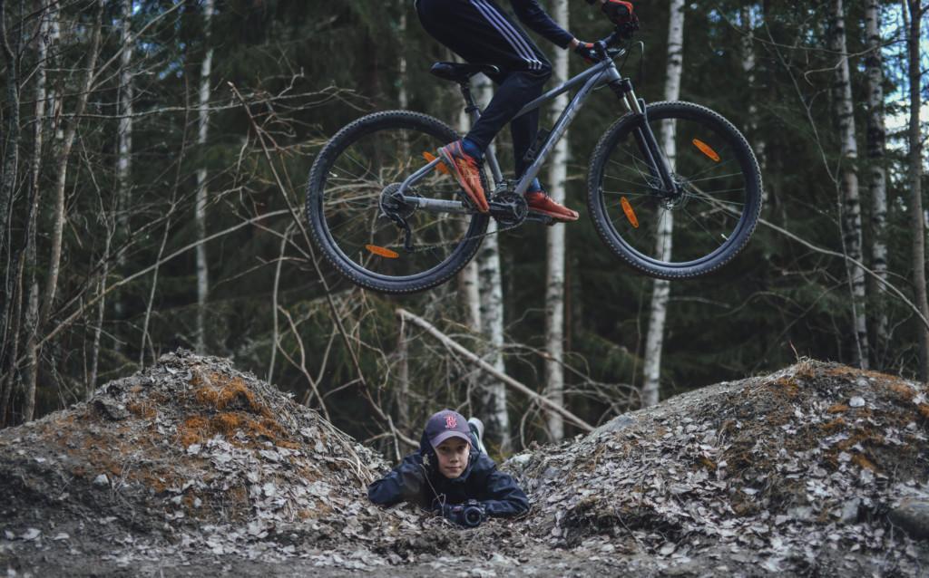 Poika makaa kahden hmaasta tehdyn hyppyrin välissä ja katsoo kameraa kamera käsissään. Toinen hyppää pyörällä hänen ylitseen.