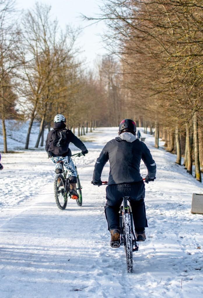 Kaksi henkilöä pyöräilee lumihangessa pyörätietä pitkin